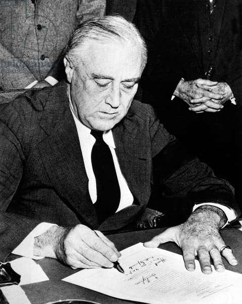 USA: President Franklin D. Roosevelt, wearing a black armband, signing the declaration of war against Japan, December 8, 1941