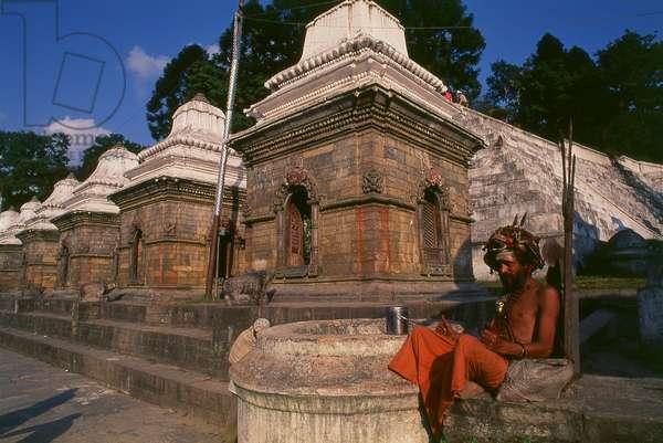 Nepal: A sadhu (holy man) next to the chaityas (small Buddhist shrines) across the Bagmati River next to the Pashupatinath Temple complex, Kathmandu (1997) (photo)