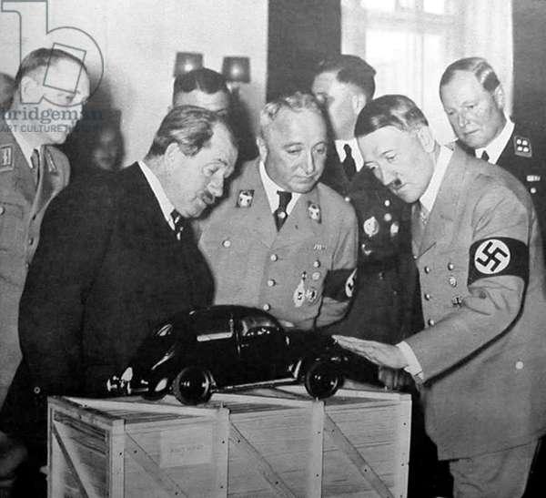 Germany: Ferdinand Porsche and Adolf Hitler examine a prototype model of the Volkswagen Beetle, 1935