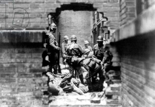 China: Imperial Japanese soldiers involved in street fighting during the Battle of Shanghai (August 13 - Nov 26, 1937) pause to examine a dead Chinese soldier.