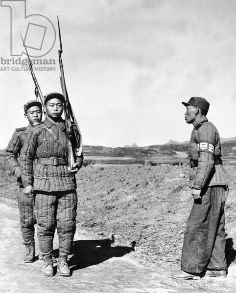 Korea: A North Korean military policeman with two North Korean soldiers near the 37th parallel, 1951