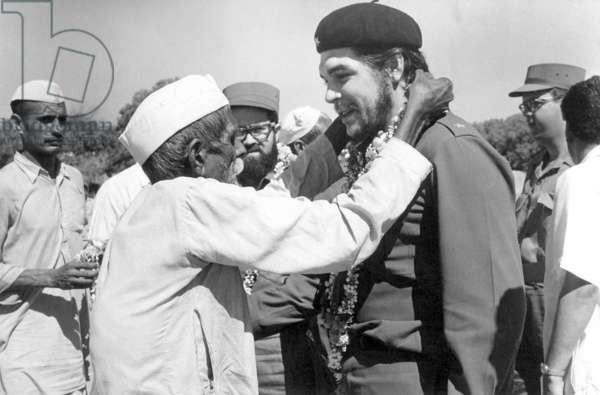 India / Cuba: An elderly villager in a Gandhi cap garlanding Che Guevara during his visit to a Community Project Area in Delhi, 1959