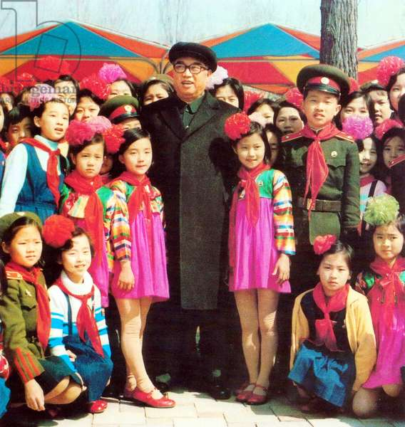 Korea: North Korea's 'Great Leader' Kim Il Sung (1912-1994), supreme ruler of the Democratic Republic of Korea (DPRK) between 1948 and 1994, posing with a group of children at Mangyongdae Fun Fair, 1982