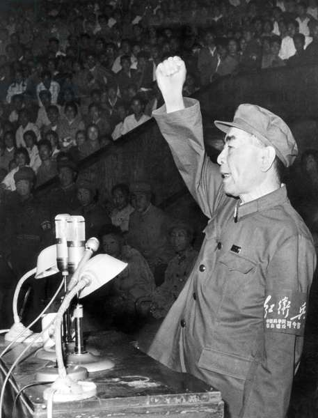 China: Chinese Premier Zhou Enlai, wearing Red Guard uniform and sporting a Red Guard armband, gives the Communist International salute at a Cultural Revolution rally in Hebei, 1966
