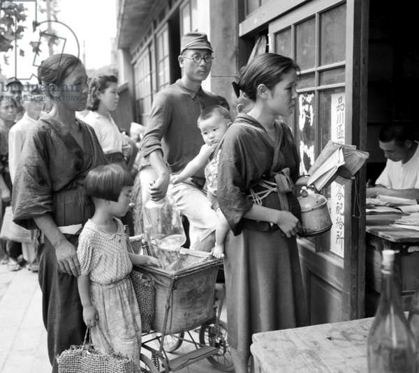 Japan: Japanese queuing for rations of beans and water following the Japanese defeat in World War II, Tokyo, 21 September 1945 (photo)