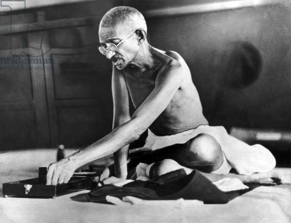 India: Mohandas Gandhi spinning with charkha wheel c. 1935