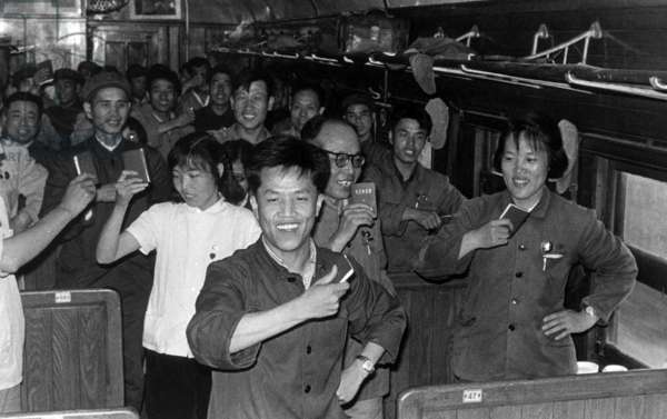 China: Scene from the Cultural Revolution (1966-1976), passengers on a train wave their copies of the 'Little Red Book' containing the selected thoughts of Chairman Mao Zedong (1967)