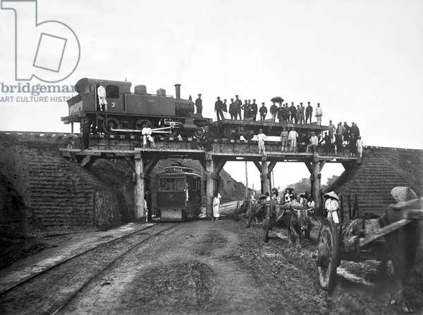 Korea: Early developments in transport, a locomotive on a bridge above a street car, probably Seoul, 1904
