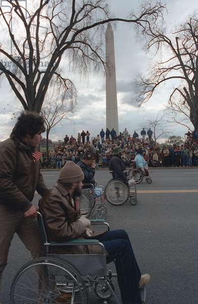 USA / Vietnam: Disabled veterans in wheelchairs pass the Washington Monument during the dedication parade for the Vietnam Veterans Memorial, 1982