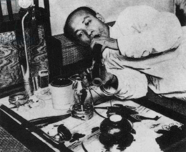 China: An opium smoker with his pipe, c. 1910