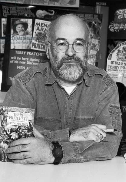 Terry Pratchett posing with a book