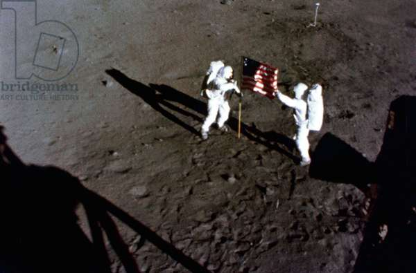 Apollo 11: N.Armstrong and E.Aldrin deploy the flag - Apollo 11: the deployment of the US flag - Deploiement of the United States flag by astronauts Neil Armstrong (left) and Edwin Aldrin. Image obtained by the camera mounted on the LEM. The deployment of the flag of the United States on the surface of the Moon is captured on film during the first Apollo 11 lunar landing mission. Here, astronaut Neil A. Armstrong, commander, stands on the left at the flagship's staff. Astronaut Edwin E. Aldrin, Jr., lunar module pilot, is also pictured. The picture was taken from film exposed by the 16 mm Data Acquisition Camera (DAC) which was mounted in the Lunar Module (LM)