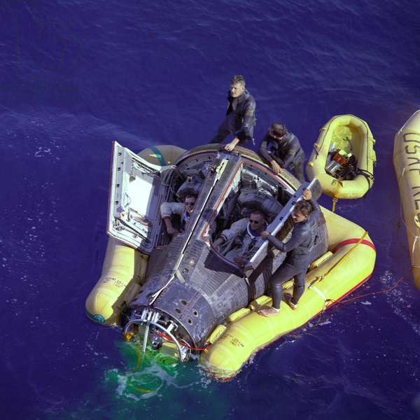 Gemini 8: return of astronauts - Gemini 8 recovery - View of the Gemini 8 capsule. On board astronauts Neil Armstrong and David Scott. 16 March 1966. Astronauts Neil A. Armstrong and David R. Scott sit with their spacecraft hatches open while awaiting the arrival of the recovery ship, the USS Leonard F. Mason after the successful completion of their Gemini VIII mission. They are assisted by U.S. Navy divers. The overhead view shows the Gemini 8 spacecraft with the yellow flotation collar attached to stabilize the spacecraft in choppy seas. The green marker dye is highly visible from the air and is used as a locating aid. March 16 1966