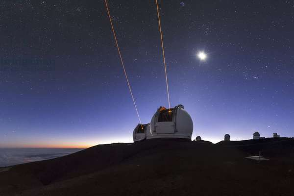 Hawaii, USA, August 9, 2015: Laser shots from Keck telescopes for adaptive optics operations. Mauna Kea Observatory, 4200 metres high, Hawaii, USA. In the sky, the Moon shines near the constellation Orion - The twin Keck telescopes beam lasers to the atmosphere for adaptive optics operation. Located near the 4205m (13800 ft) summit of Mauna Kea volcano on the Big Island of Hawaii, the observatory is recognized as one of the world's premier astronomical research facilities. Hawaii's isolation in the mid-Pacific Ocean and the high elevation of Maunakea makes it one of the best locations on Earth for astronomical observations. The Moon, next to Orion and Taurus, appears above the rising morning twilight