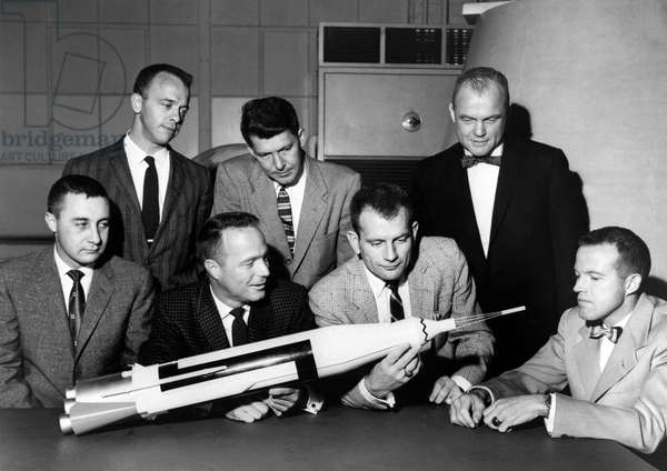Mercury: Portrait of Astronauts - Mercury: Astronauts and Capsule Model - The Mercury 7 astronauts inspecting Mercury model. Front row (from l. to r.): Virgil Grissom. Scott Carpenter, Donald Slayton and Gordon Cooper. Back row (from l. to r.): Alan Shepard, Walter Schirra and John Glenn