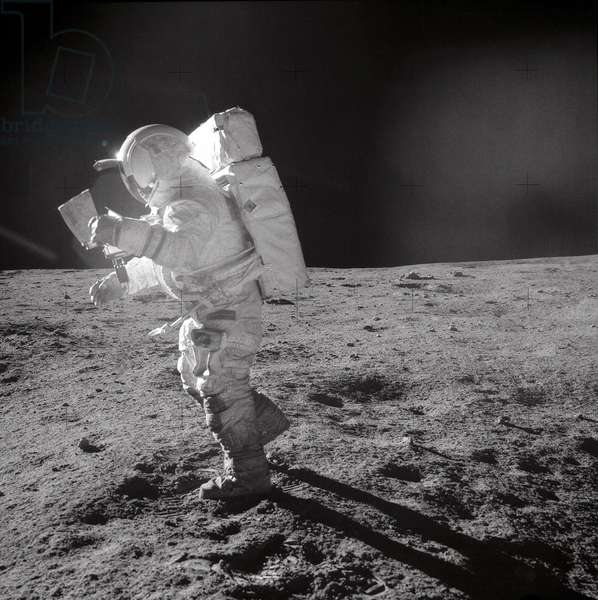 Apollo 14: E. Mitchell sur la Lune - Apollo 14: E. Mitchell moonwalk - Sortie extravehiculaire d'Edgar Mitchell equipe d'une carte. 05/02/1971. Astronaut Edgar D. Mitchell, lunar module pilot, moves across the lunar surface as he looks over a traverse map during an extravehicular activity (EVA). Lunar dust can be seen clinging to the boots and legs of the space suit. Astronauts Alan B. Shepard Jr., commander, and Mitchell explored the lunar surface while astronaut Stuart A. Roosa, command module pilot, orbited the moon in the Command and Service Modules (CSM)