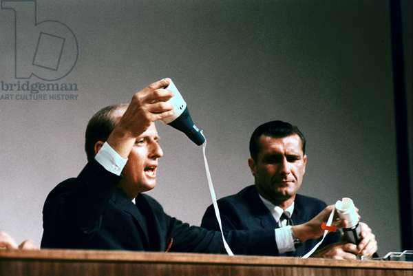 Gemini 11: press conference - Gemini 11 post flight press conference - Charles Conrad (g.) and Richard Gordon explain the connection operations between the Gemini 11 ship and the Agena target vehicle rocket. 26 Sep 1966. Charles Conrad (left) and Richard Gordon demonstrate tether procedure between Gemini 11 spacecraft and the Agena target vehicle at the post flight press conference. Sep 26 1966