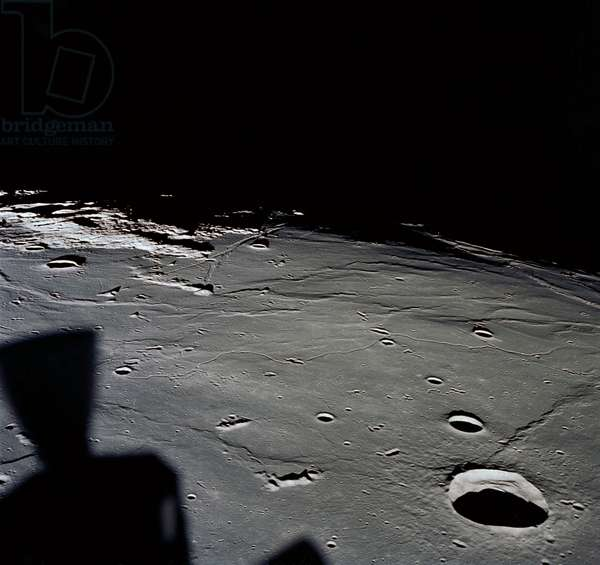 Apollo 11: Sea of Tranquility - Apollo 11: Sea of Tranquility - Apollo 11 07/69 - The shadow of the control module on the Moon, the Maskelyne crater is visible at the bottom of the picture. 20/07/1969. The approach to Apollo Landing Site 2 in southwestern Sea of Tranquility is seen in this photograph taken from the Apollo 11 Lunar Module (LM) in lunar orbit. When this picture was made, the LM was still docked to the Command and Service Modules. Site 2 is located just right of center at the edge of darkness. The crater Maskelyne is the large one at the lower right. Hypatia Rille (U.S.1) is at upper left, with the crater Moltke just to the right (north) of it. Sidewinder Rille and Diamondback Rille extend from left to right across the center of the picture. This view looks generally west