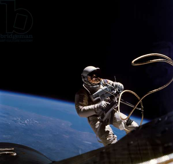 Gemini 4: release of Ed.White - Gemini 4: Ed White EVA - release of Edward White in space on June 3, 1965. June 3, 1965 Gemini 4 Edward White during first EVA performed during Gemini 4 flight Astronaut Edward H. White II, pilot for the Gemini - Titan 4 space flight, floats in zero gravity of space. The extravehicular activity was performed during the third revolution of the Gemini 4 spacecraft. White is attached to the spacecraft by a 25 - ft. umbilical line and a 23 - ft. tether line, both wrapped in gold tape to form one cord. In his right hand White carries a Hand - Held Self - Maneuvering Unit (HHSMU). The visor of his helmet is gold plated to protect him from the unfiltered rays of the sun