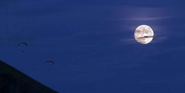 Full Moon and Paragliders - Full Moon with paragliders - Full Moon Sunrise. Two paragliders are rising from the hill. The Full Moon rises in Germany. Two paragliders are flying off from a hill top