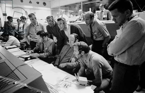 Apollo 13: Control Room - View of Mission Control Center during the Apollo 13 problem - View of the control room as a group of astronauts and controllers guide the crew of Apollo 13 trying to return to Earth after the explosion of an oxygen tank. 14/04/1970. A group of eight astronauts and flight controllers monitor the console activity in the Mission Operations Control Room of the Mission Control Center during the Apollo 13 lunar landing mission. Seated, left to right, are MOCR Guidance Officer Raymond F. Teague; Astronaut Edgar D. Mitchell, and Astronaut Alan B. Shepard Jr., Standing, left to right, are Scientist - Astronaut Anthony W. England; Astronaut Joe H. Engle; Astronaut Eugene A. Cernan; Astronaut Ronald E. Evans; and M.P. Frank, a flight controller. When this picture was made, the Apollo 13 moon landing had already been cancelled, and the Apollo 13 crewmen were in transearth trajectory attempting to bring their crippled spacecraft back home. 14 April 1970