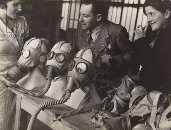 A sales[woman] in a drug store, where gas masks are sold, tries to praise the latest 'creations' in gas masks, 1934 (gelatin silver print)