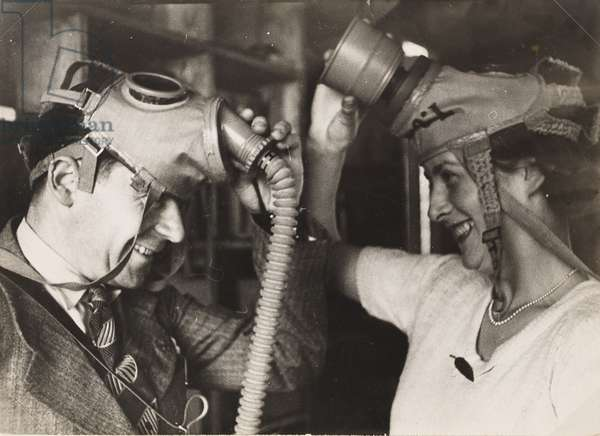 Man and woman holding gas masks on their heads, smiling at each other, 1934 (gelatin silver print)