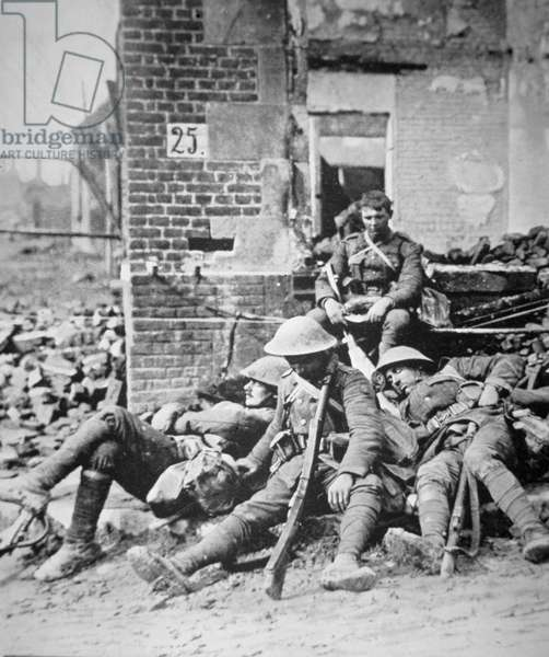 British troops resting after pushing Germans from a town during the Allied offensive in southwest Flanders, August 1917 (b/w photo)
