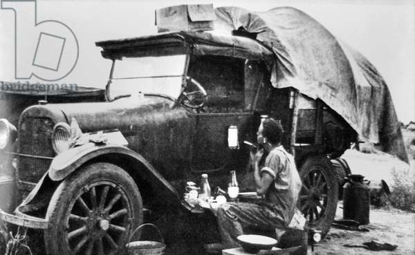 Migratory worker on the road, pausing whilst journeying for work, 1938 (b/w photo)