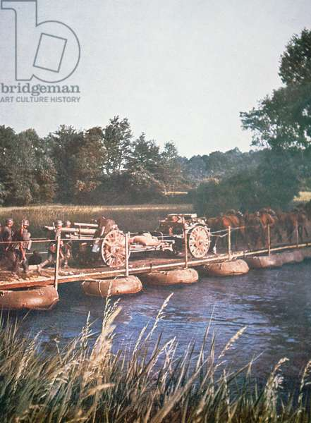 A team of horses pulls a 105mm howitzer across a pontoon bridge during the German invasion of France, 1940 (photo)
