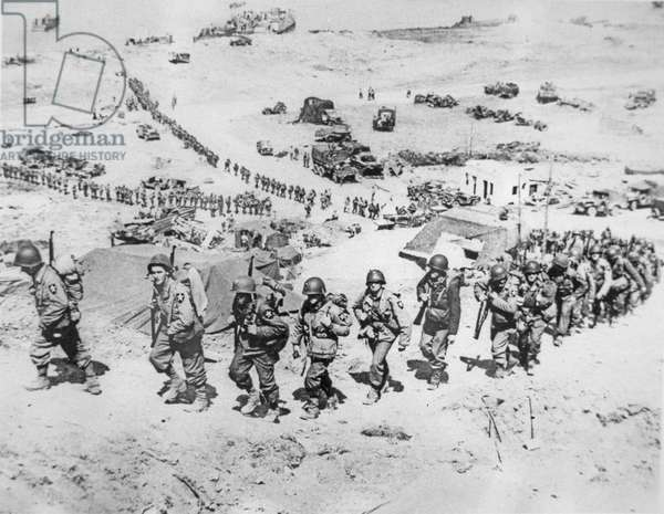 American reinforcements of US 2nd Infantry Division march inland from Easy Red sector of Omaha Beach, near Saint Laurent, 8th June 1944 (b/w photo)