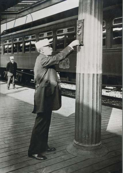 A conductor signalling the imminent departure of the 'Royal Blue' train at Washington D.C. in 1910 (b/w photo)