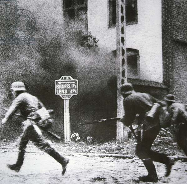 German infantry advance swiftly through a French village some 25 miles from Dunkirk, May 1940 (b/w photo)