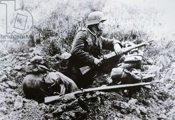 German NCO in a foxhole armed with the short Kar 98k carbine, K98b Mauser rifle nearby, France, 1940 (b/w photo)