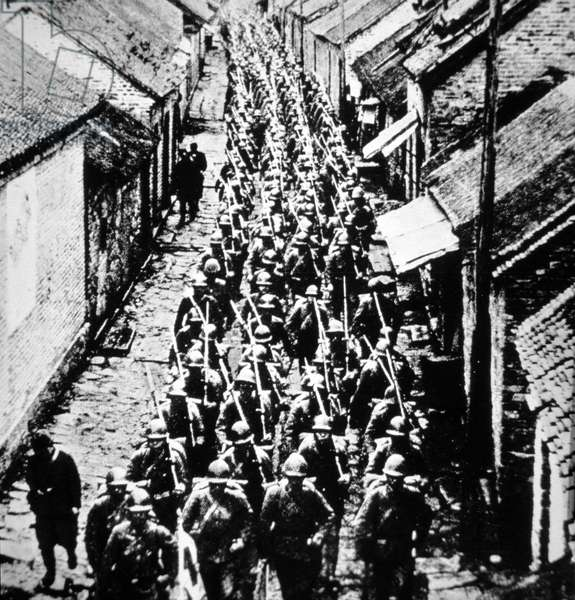 Japanese troops march through a town in Manchuria, 1932 (b/w photo)