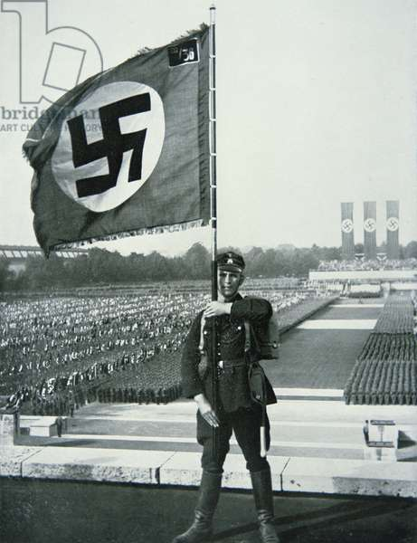 SS Trooper holding a Nazi Flag at a Nuremberg Rally, 1933 (b/w photo)