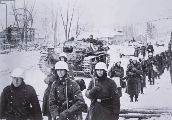 German infantry in winter clothing moving in a column supported by a StuG III self-propelled assault gun during the invasion of Russia, 1941 (b/w photo)