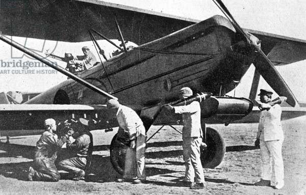 Japanese plane being loaded with bombs in Manchuria, 1933 (b/w photo)