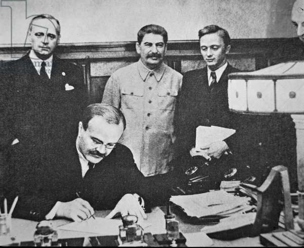 Molotov signing the German-Soviet Pact, with Stalin and von Ribbentrop looking on, 1939 (b/w photo)