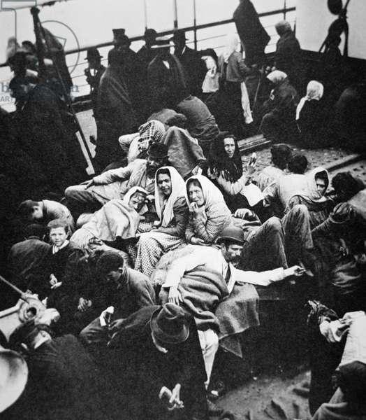 Steerage passengers enjoying fresh air on deck as their ship enters New York harbour, c.1905 (b/w photo)