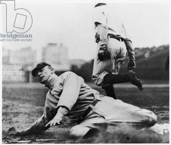 Ty Cobb, star of the Detroit Tigers, stealing a base in the 1910-11 American League (b/w photo)