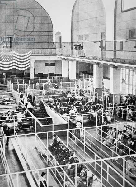 Immigrants waiting in the Registration Hall on Ellis Island, New York, 1910 (b/w photo)