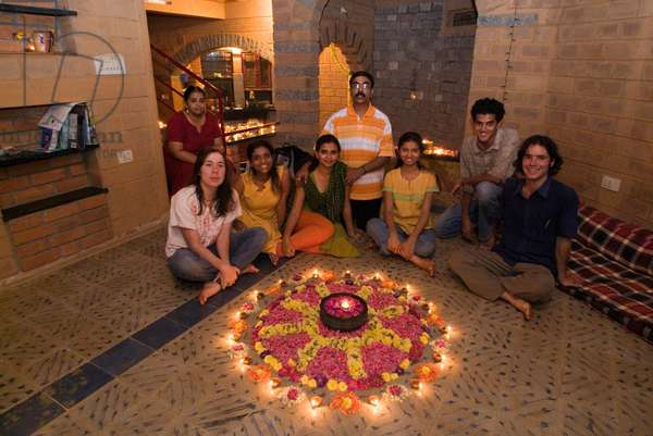Indians and Westerners celebrating Diwali together with a Rangoli on the floor (photo)