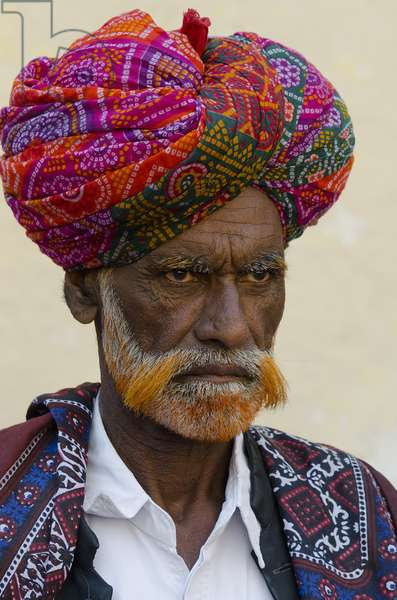 Portrait of male elder (with muti-coloured turban and hennaed grey beard) and musician from the Jaisalmer Jogi community/caste,