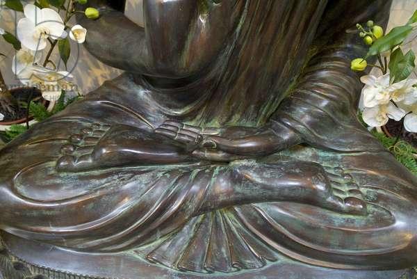 Feet of Buddha sculpture in full lotus position, left hand mudra symbolizing meditation, Harnham Buddhist Monastery, Northumberland, UK (photo)