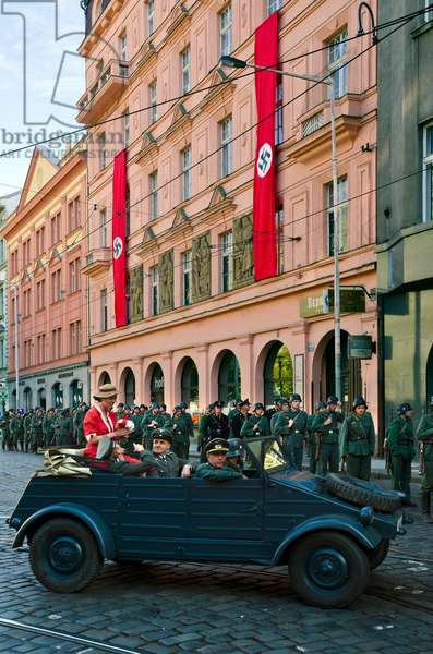 Filmset in Prague: Nazi jeep with officers & woman with flower bouquet, SS troops, building with swastika flags,(Chinese production), Senovazne Square, Prague, Czech Republic(photo)
