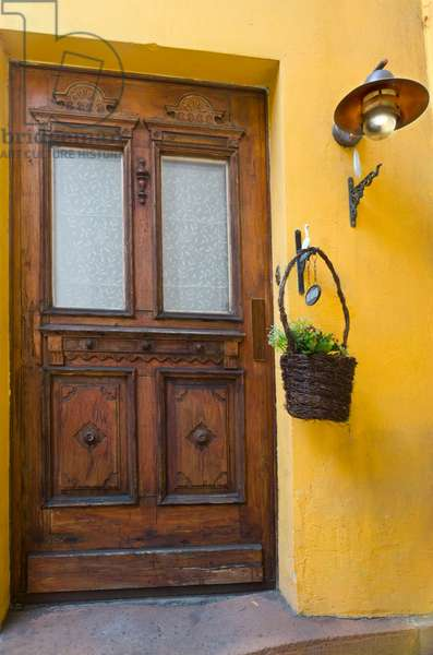 Old carved wooden housedoor with lamp and hanging basket in yellow wall, Bad Ems, Rhein-Lahn District, Rhineland-Palatinate, Germany(photo)