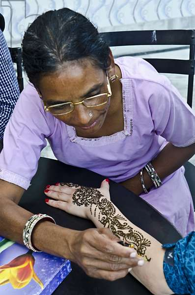 Woman applying mehndi to arm of other woman,