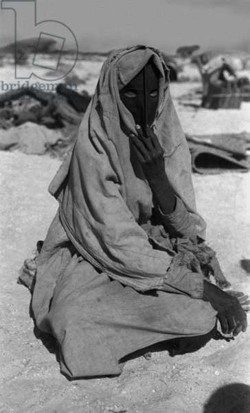Portrait of a woman of the Harasis Bedouin sitting on the ground in the region between Boi well and Yisub well in the Jiddat al Harasis, Oman, February 4–14, 1947 (b/w photo)