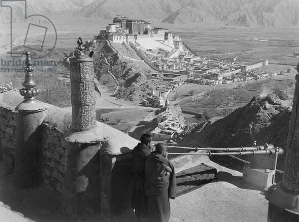 Monks blowing ceremonial trumpets or radung from the roof of the Chakpori Medical College, Lhasa, Tibet, 2nd October 1936 (b/w photo)